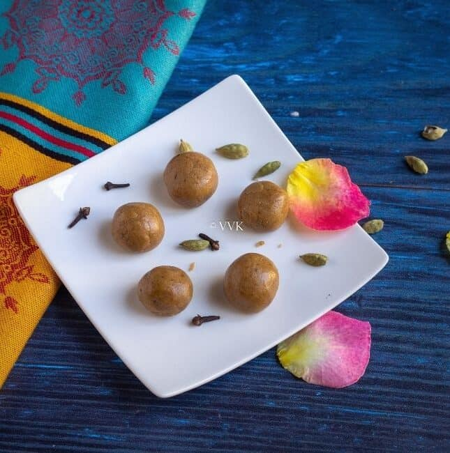 square image of akki unde in a white plate with cardamom and cloves and rose petals as garnish