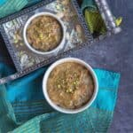 square image of banana biscuit halwa served in two white bowls with nuts on the side