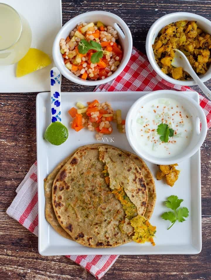 overhead shot of broccoli carrot lunch paratha thali
