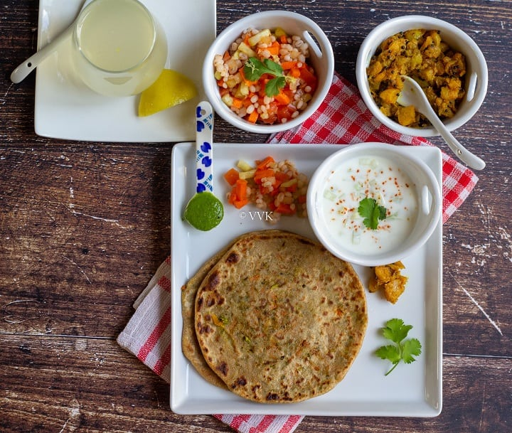 broccoli carrot paratha thali with all the condiments salad, pickle, chutney, and drink