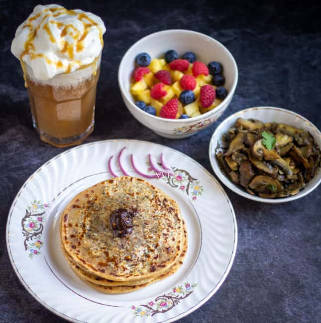 square image of cheese paratha thali with mushrooms, butterbeer and fruit salad