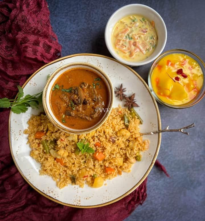 veg biryani served with mushroom gravy and raita with fruit custard as a dessert