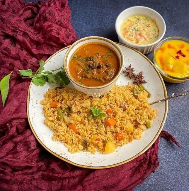 square image of chettinad biryani thali served with mushroom gravy, raita and custard