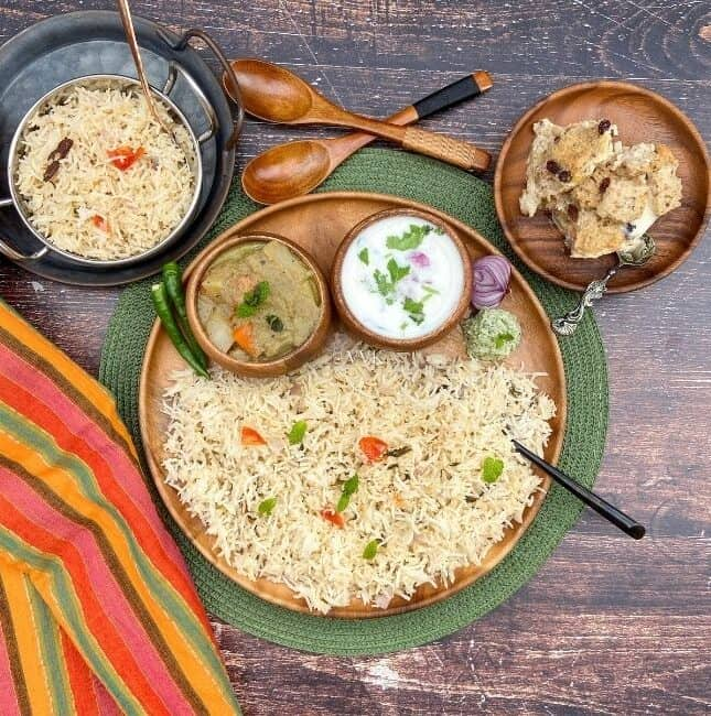 square image of overhead shot of coconut milk pulao platter with assorted sides served on a wooden plate