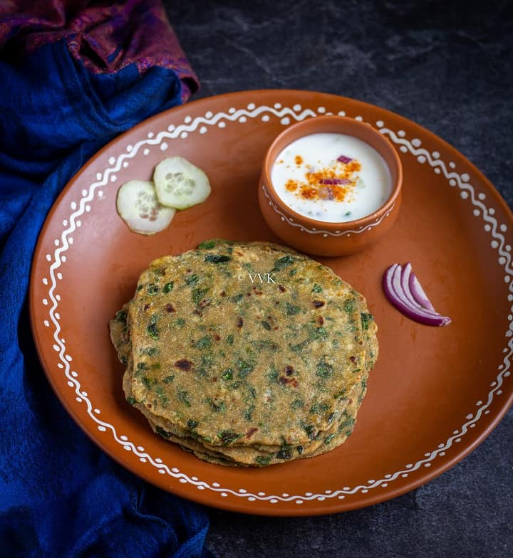 simple methi paratha in a clay plate served with raita
