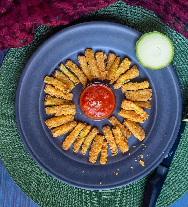 air fryer zucchini fries places on blue plate with marinara in the middle