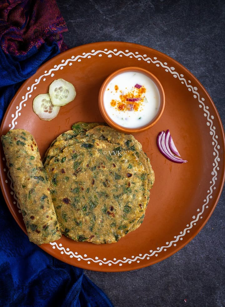 methi paratha in a terracotta with one rolled