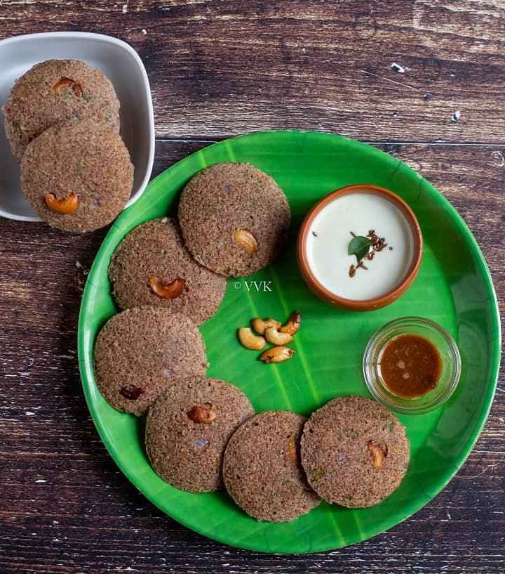 overhead shot of ragi idli served in green plate with chuntey and podi