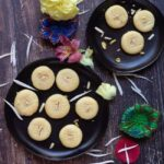 milk peda in two black plates sprinkled with white flowers all over