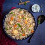 mixed vegetable pulao in a big bowl served with raita