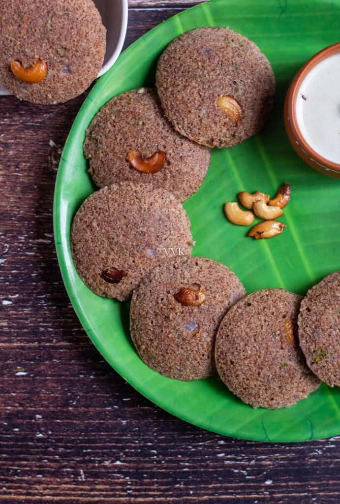 close up shot of ragi idli served in green plate with cashews on the side