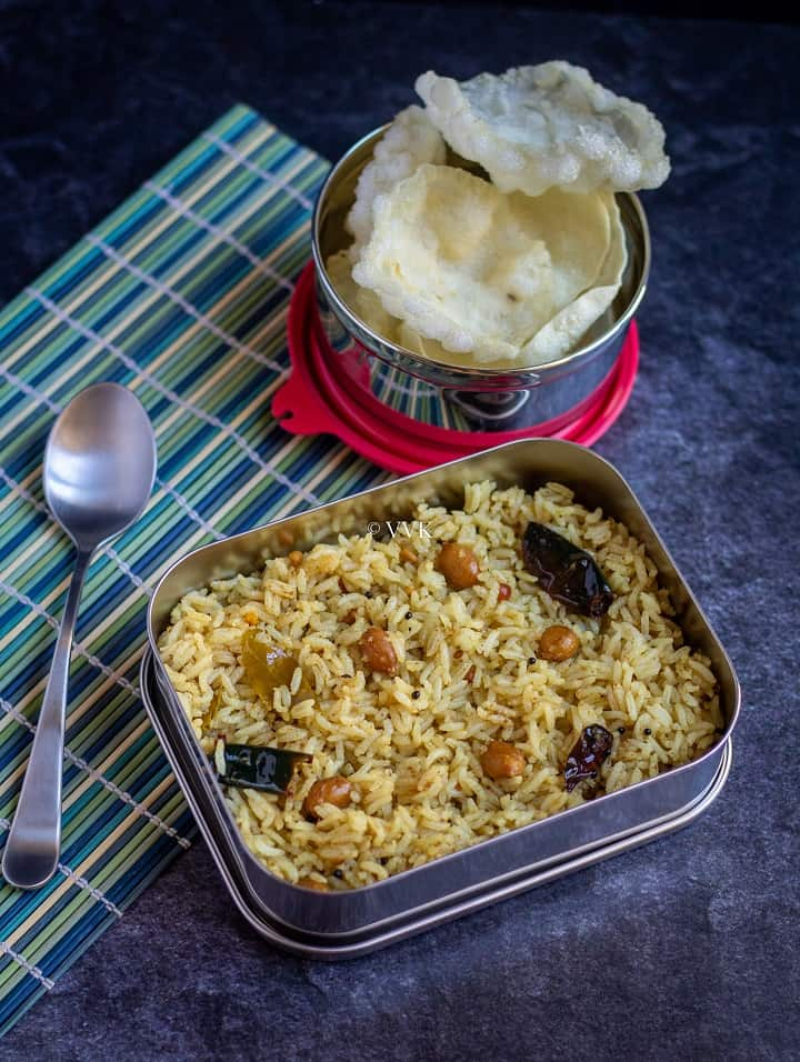 slanting shots of tamarind rice in lunch box with a spoon the side with fryums