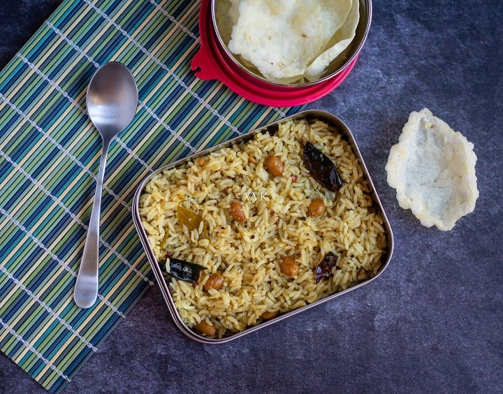tamarind rice recipe for lunch box with a spoon and some fryums placed on a green mat