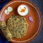 methi paratha in clay plate with raita