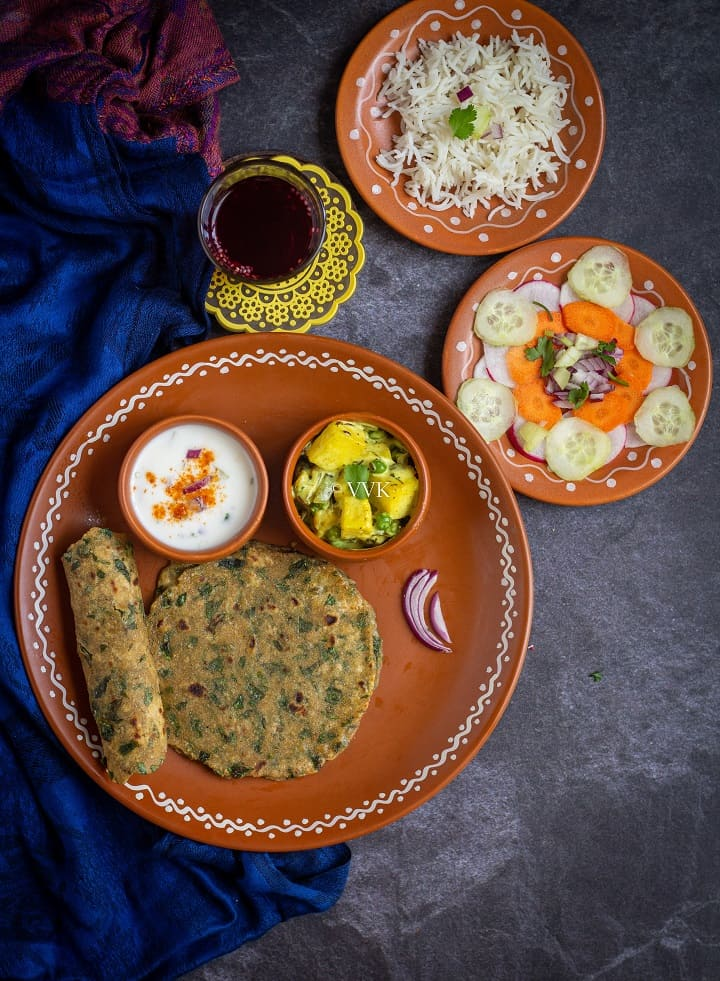 methi paratha thali with rice, paneer curry, salad and iced tea