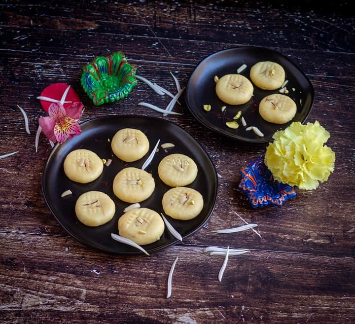 microwave instant milk peda placed on black plates with flowers on the side