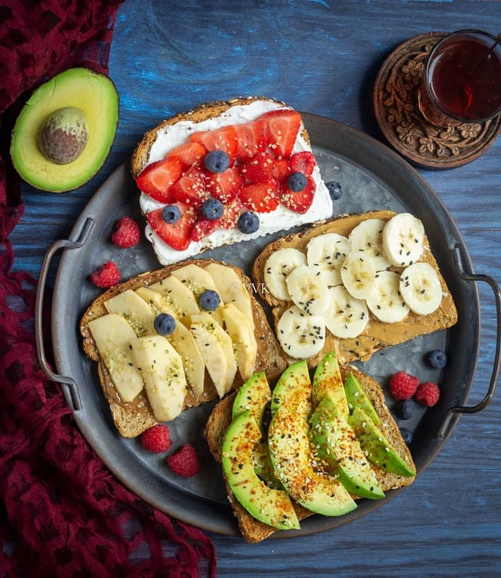 overhead shot of breakfast toast placed on a metallic tray with cut avocado and tea on the sides