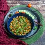 oats bhel in a blue bowl placed on a rustic tray with cucumbers on the side