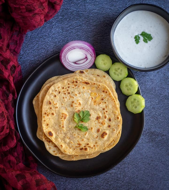 paneer paratha stacked in black plate with cut onions and cucumbers with raita on the side