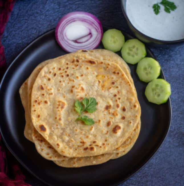 square image of paneer paratha with some raita, cut onions and cucumbers