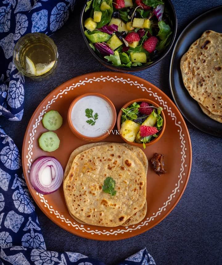 overhead shot of paneer paratha thali with raita, salad and pickle