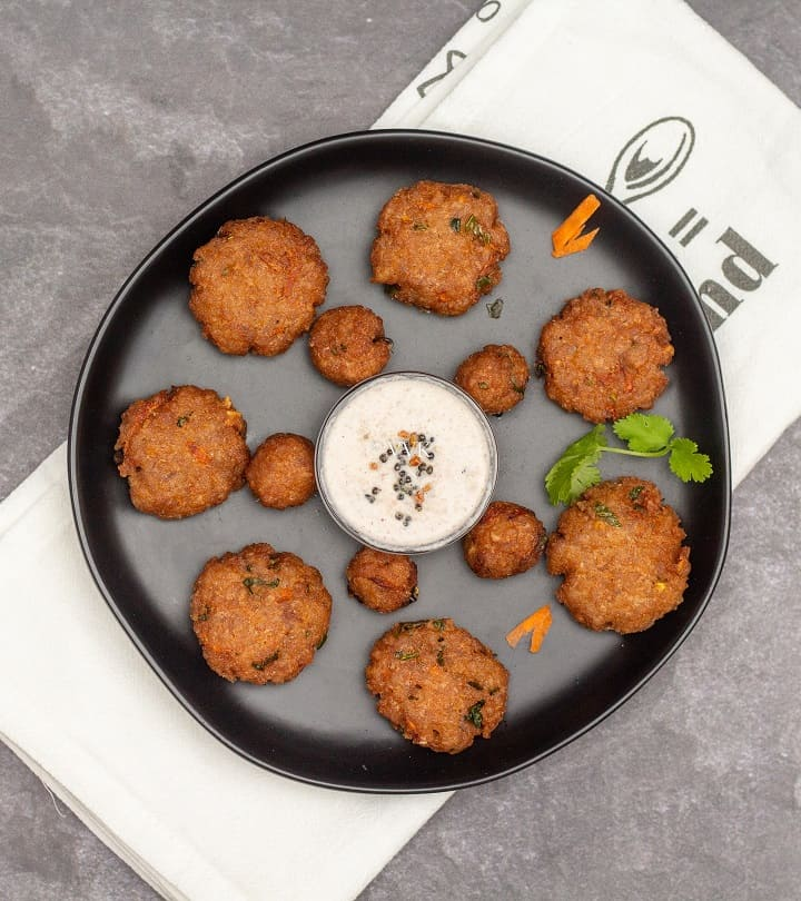 overhead shot of poha vada with coconut chutney in the center served on the black plate