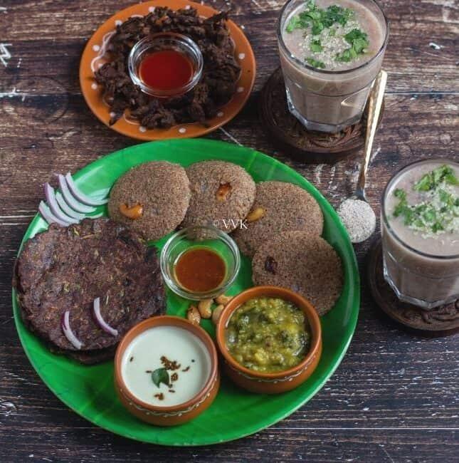 square image of ragi platter with ragi idli, adai, pakora and kanji served with chutney and spinach sambar