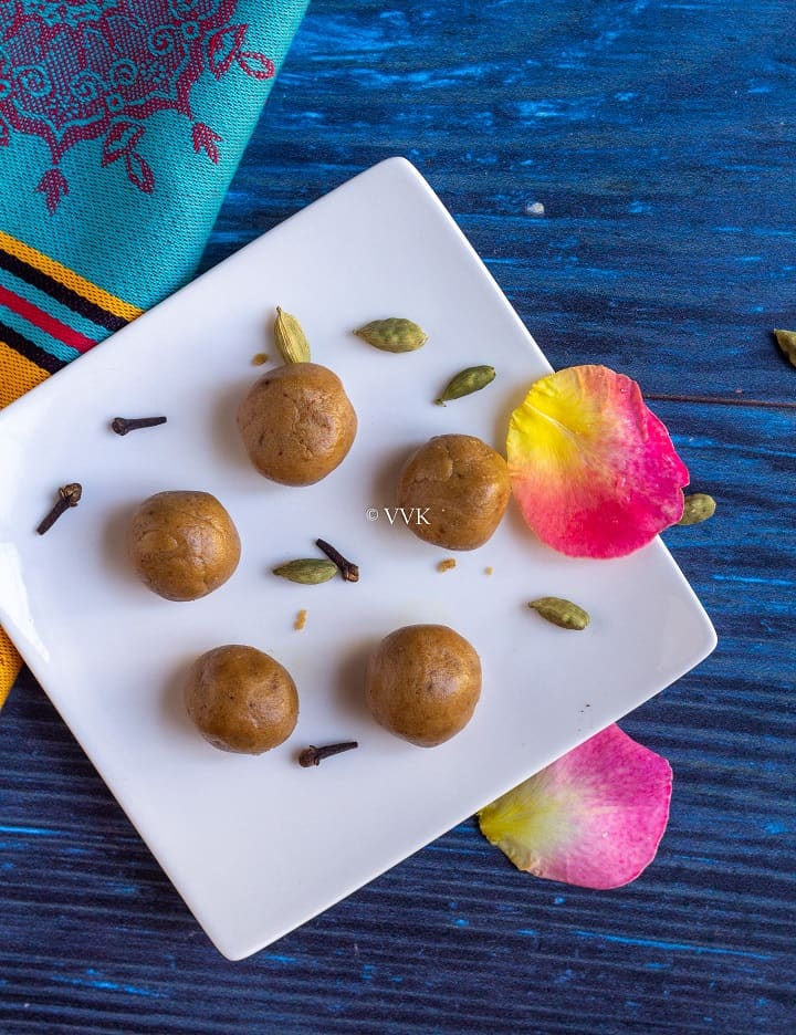 rice flour laddu in a white plate with cardamom and cloves and rose petals as garnish