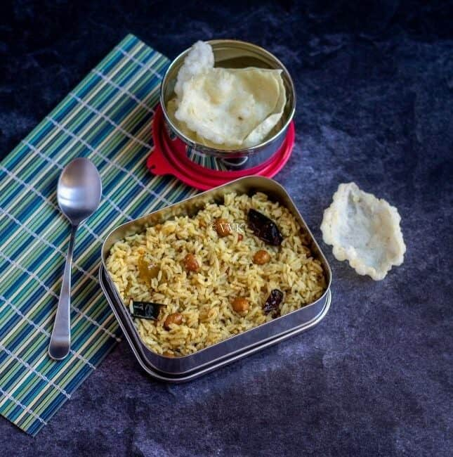 tamarind rice in lunch box with fryums on the side and placed on a mat with the spoon on the side