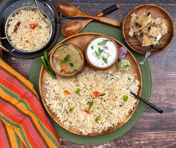 overhead shot of coconut milk pulao platter with assorted sides served on a wooden plate placed on a green mat