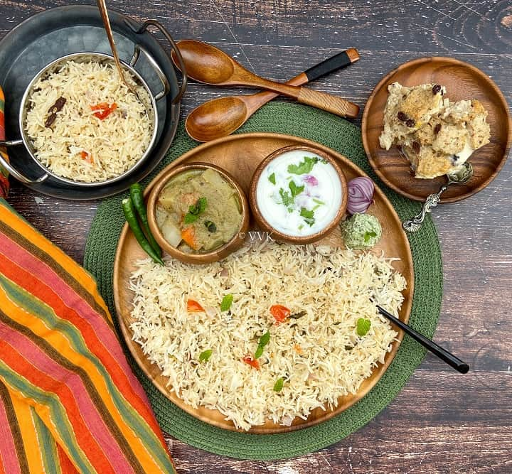 overhead shot of coconut milk pulao platter with assorted sides served on a wooden plate