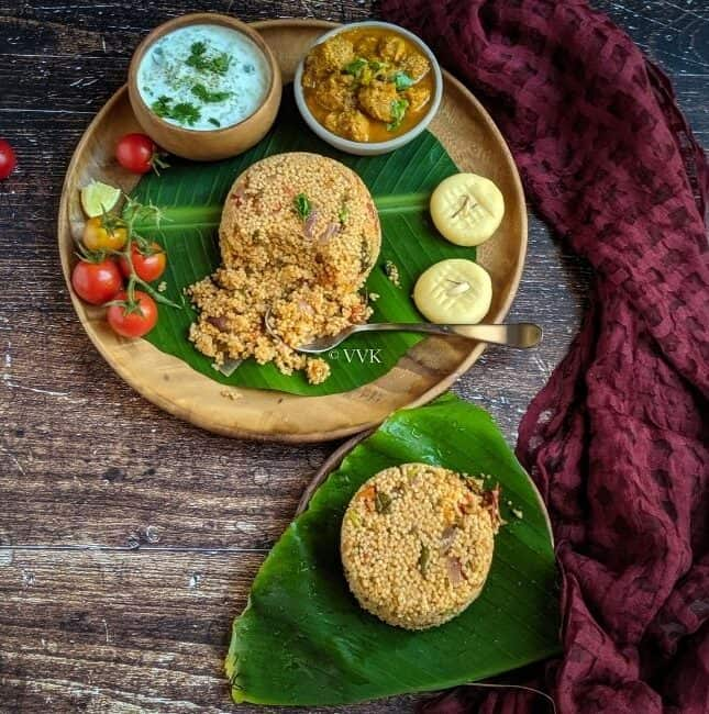 biryani served in a wooden plate lined with banana leaf with raita, gravy and sweet