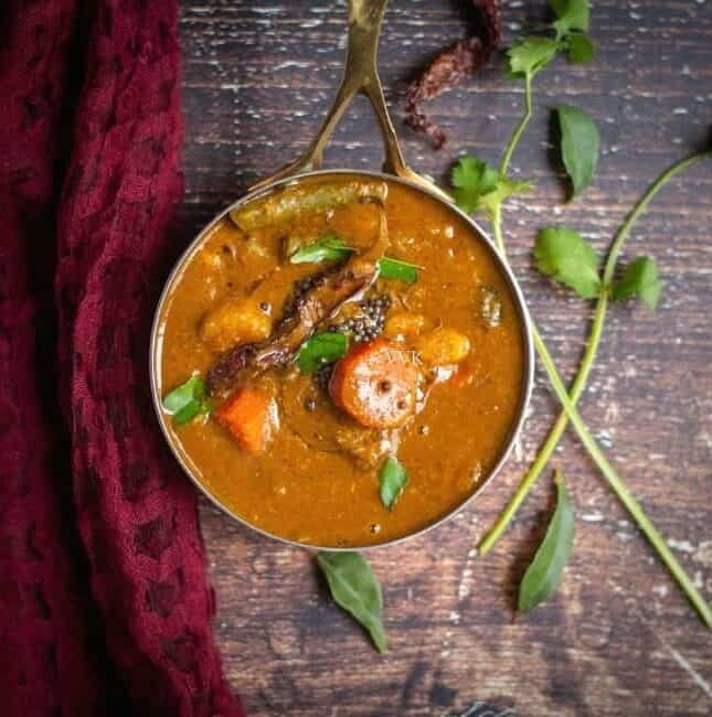 square image of thiruvathirai sambar with a maroon fabric on the side with some greens on the other side