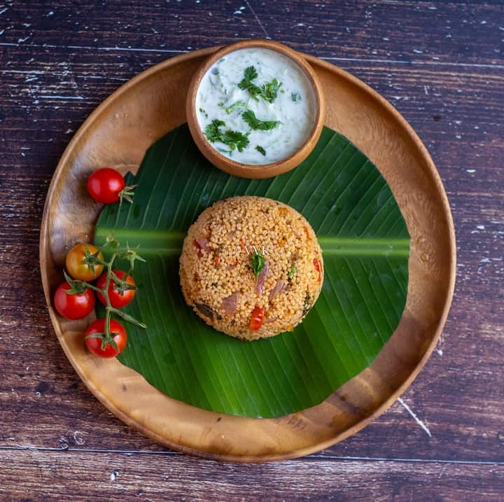 millet biryani served on a wooden plate lined with banana leaf