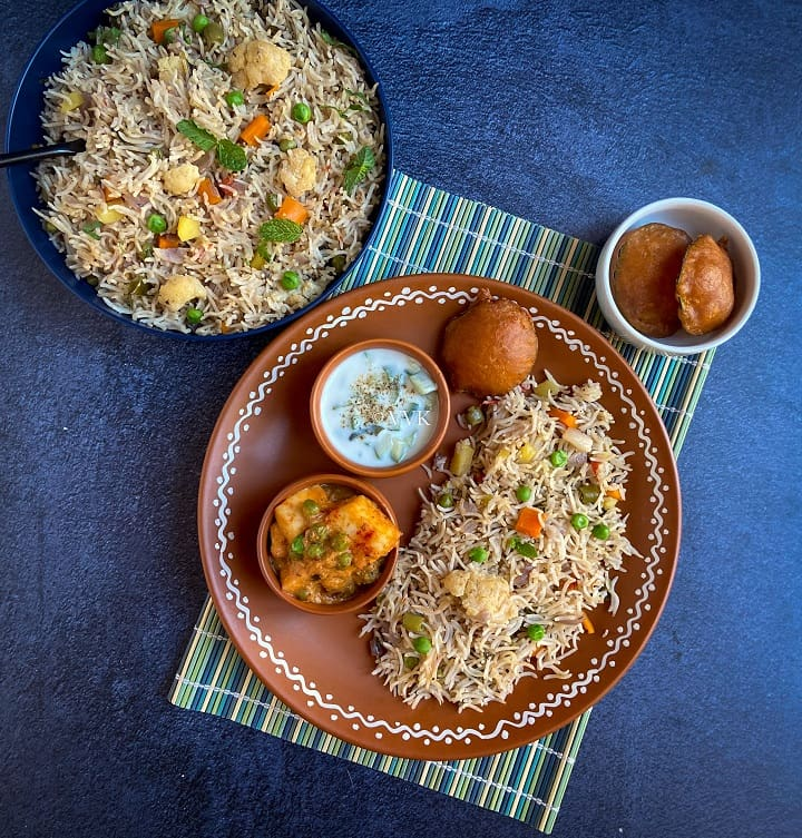 simple pulav platter with veg pulao, raita, matar paneer and bajji served in a terracotta plate