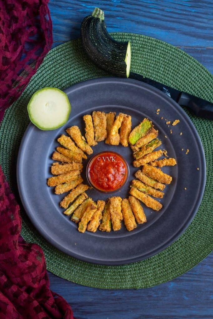 overhead shot of zucchini fries served on a rustic blue plate with marinara in the middle