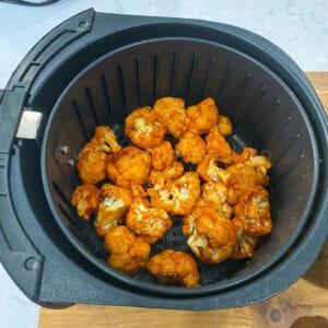 coated cauliflwer in the air fryer basket