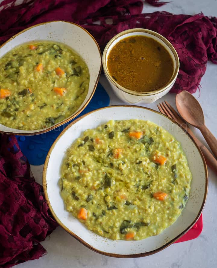 instant pot khichdi served in white serveware with wooden spoons and vathal kuzhambu