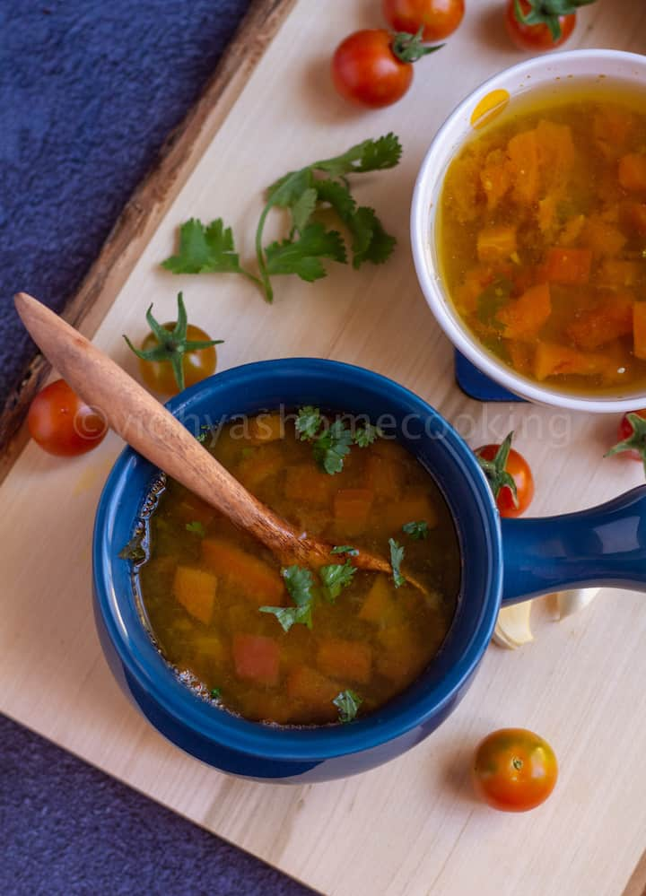 Instant Pot thakkali rasam served in a blue bowl with a wooden spoon side