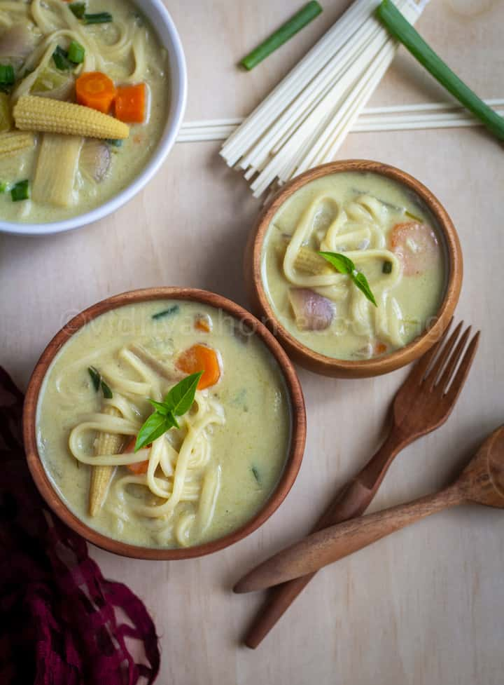 easy Thai curried noodle soup served in wooden bowls with spoon and fork on the side