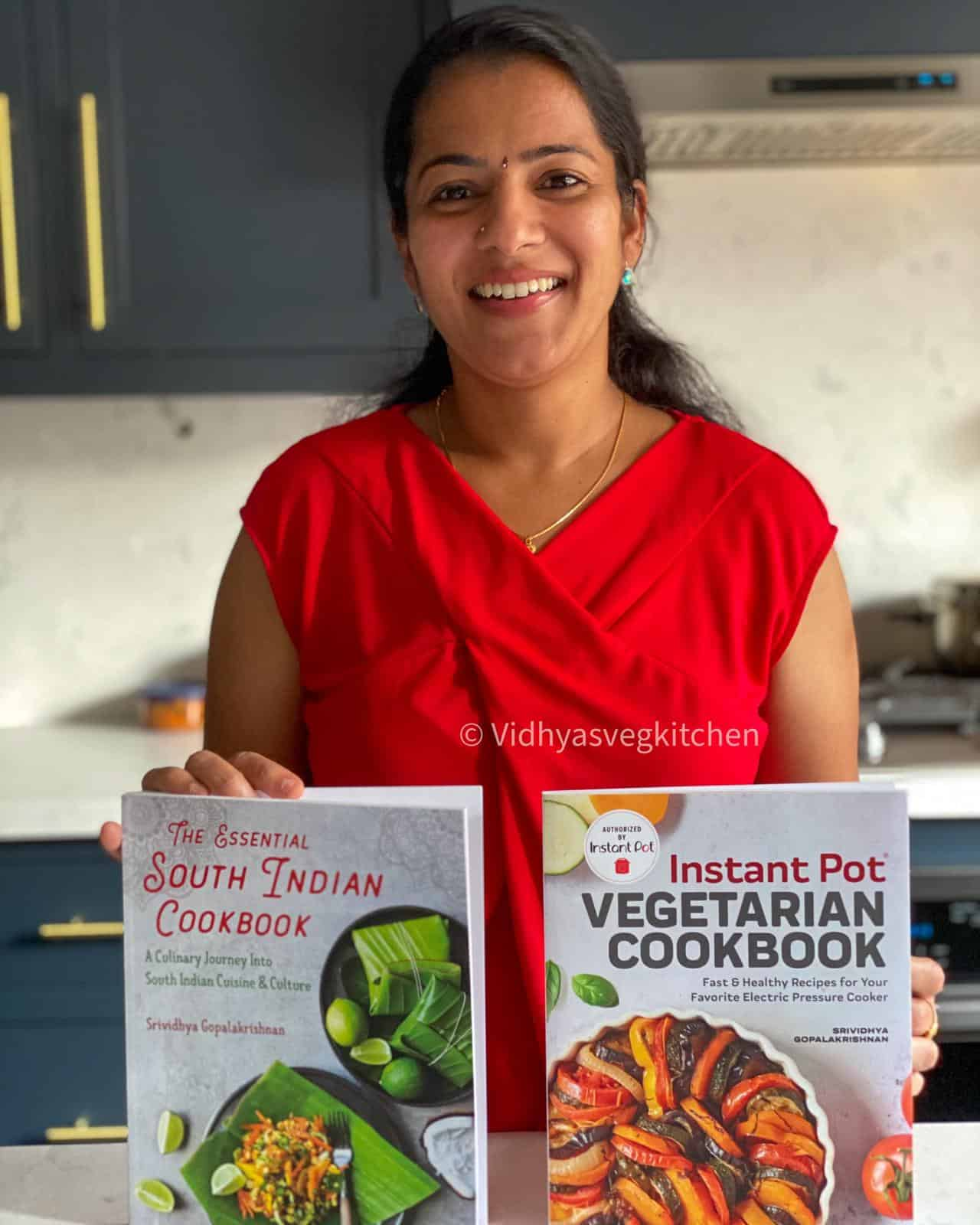 Author of the blog, Vidhya, holding two new cookbooks with plenty of healthy and delicious Indian recipes