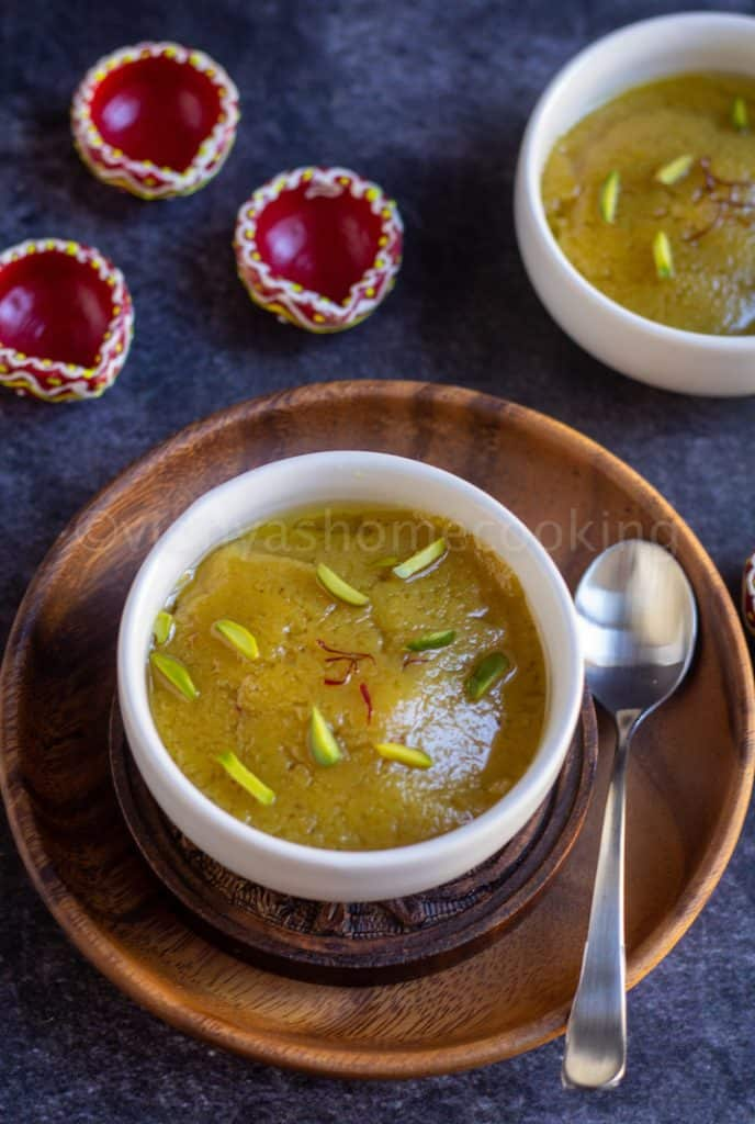 close up shot of badam halwa in a white bowl placed on a wooden plate with spoon