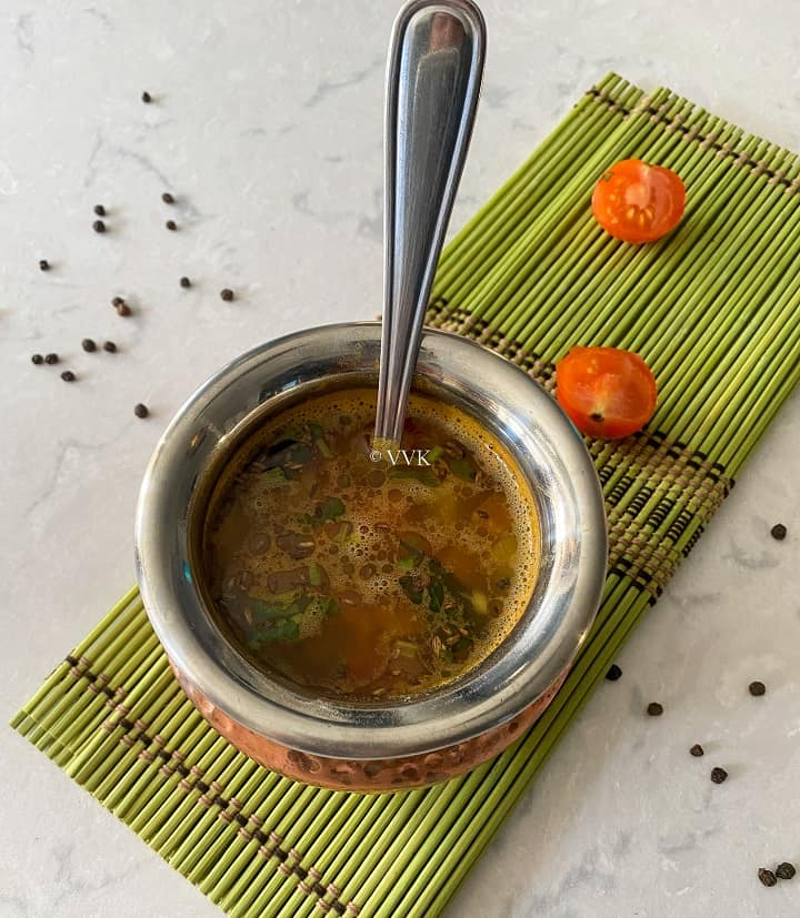 pineapple rasam in a traditional brassware placed on a green mat with tomatoes on the side