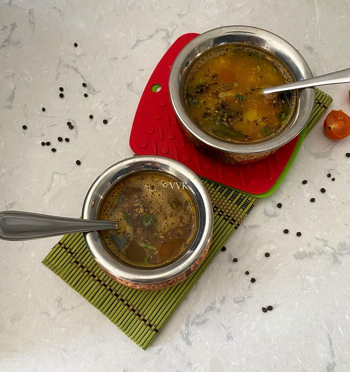 overhead shot of annasi rasam served in two copper servewares