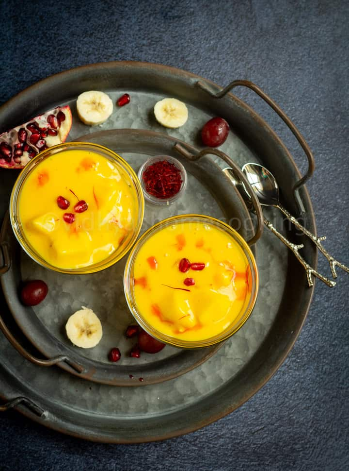 overhead shot of fruit custard served in two bowls with fruits on the side