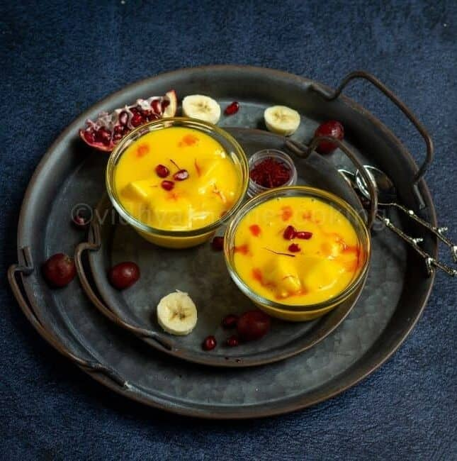 square image of fruit custard served in two bowls placed on rustic tray