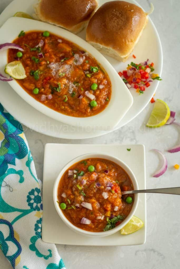 close up shot of pav bhaji placed on a white bowl with a spoon inside