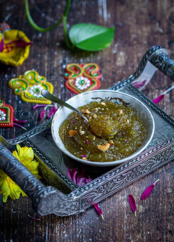 zucchini halwa served on a bowl placed on a silver tray with a spoon inside