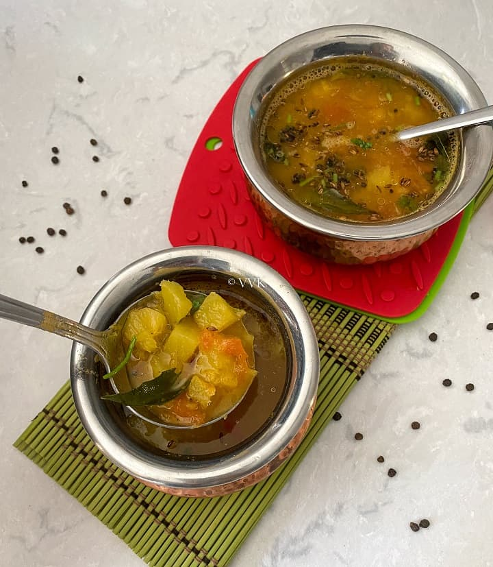 close up shot of pineapple rasam served in two copperserveware
