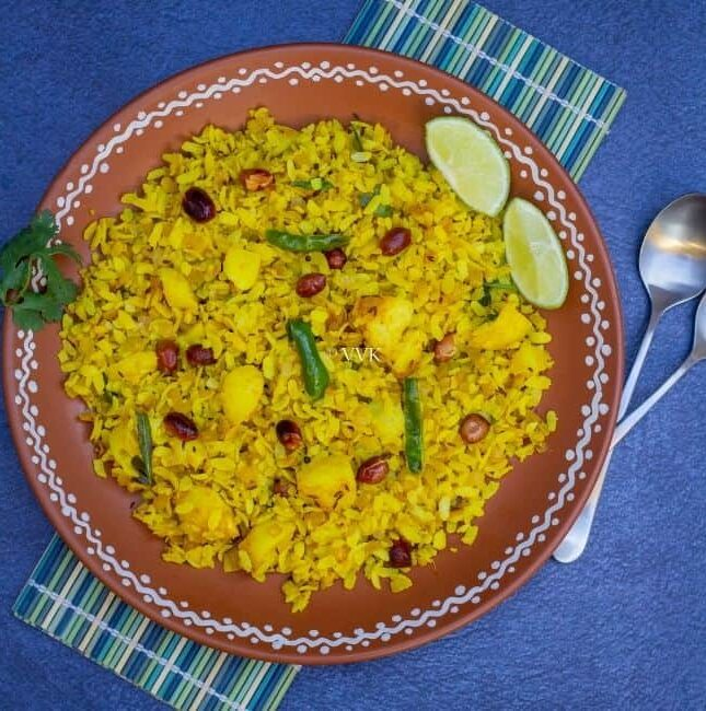 square image of poha served in terracotta plate placed on a mat with spoons on the side and with some lemon wedges